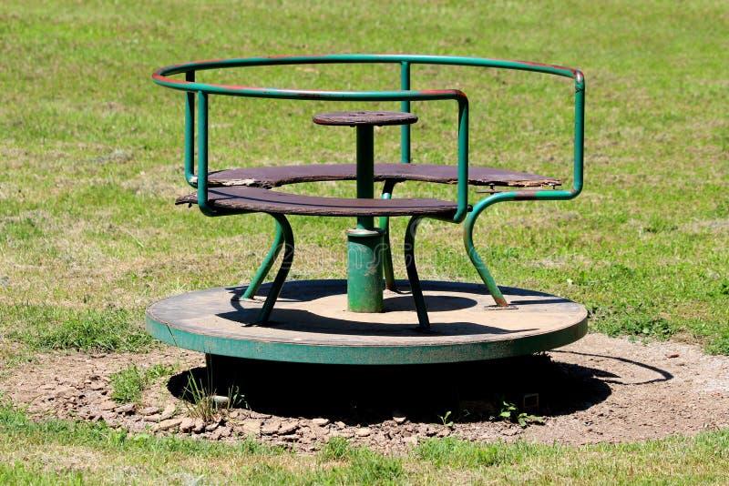 Oud uitstekend retro gedeeltelijk geroest openlucht openbaar speelplaatsmateriaal dat van metaal en gebarsten hout in vorm van ro royalty-vrije stock fotografie