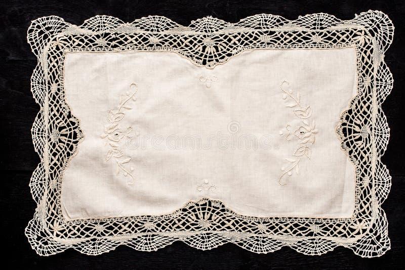 Oud uitstekend servet met kantgrens op de zwarte houten lijst royalty-vrije stock afbeeldingen