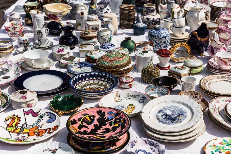 Oud uitstekend voorwerpen en meubilair bij een garage sale bij de vlo m stock fotografie