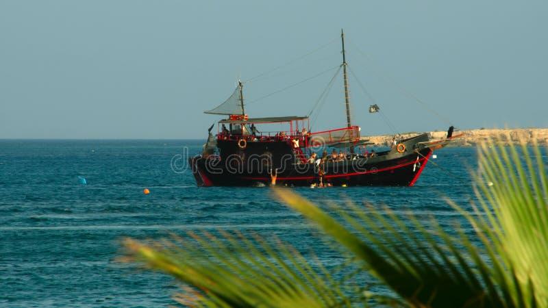 oud varend schip Mening door de bovenkanten van de palmen stock foto