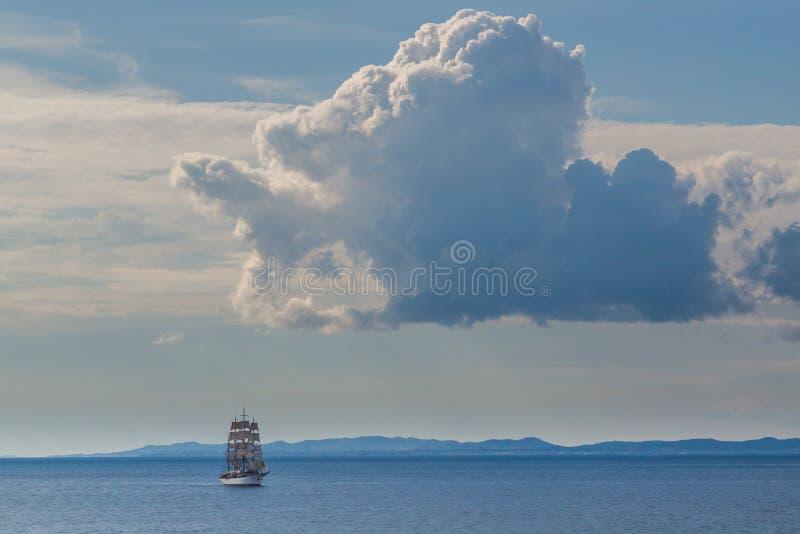 Oud varend schip onder wolken blauwe overzees en hemel royalty-vrije stock afbeeldingen