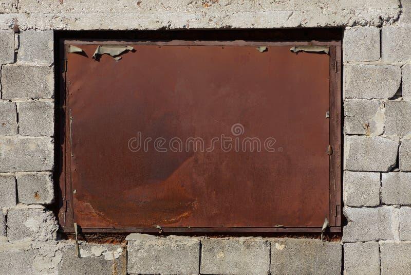 Oud venster dat omhoog met een roestig blad van ijzer op een grijze bakstenen muur wordt ingescheept stock foto