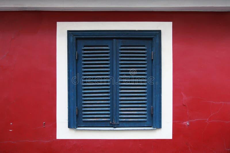 Oud venster met gesloten blauwe jaloezie royalty-vrije stock fotografie