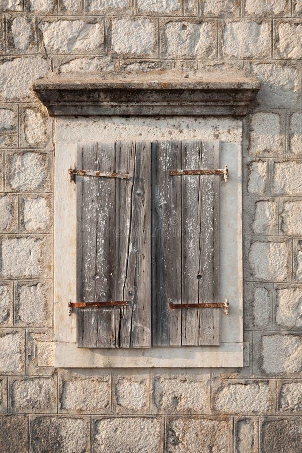 Oud venster met gesloten houten jaloezie stock afbeeldingen