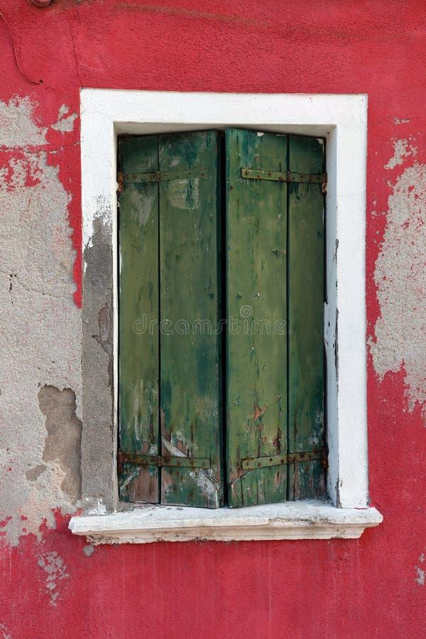 Oud venster met groene blinden op rode muur stock foto