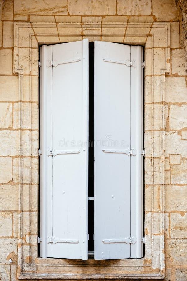 Oud venster met houten witte geschilderde blinden stock foto