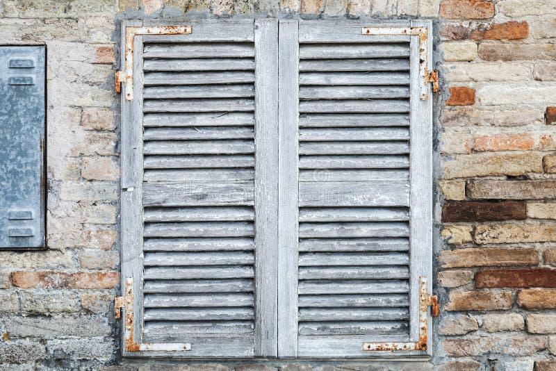 Oud venster met witte gesloten houten blinden stock foto's