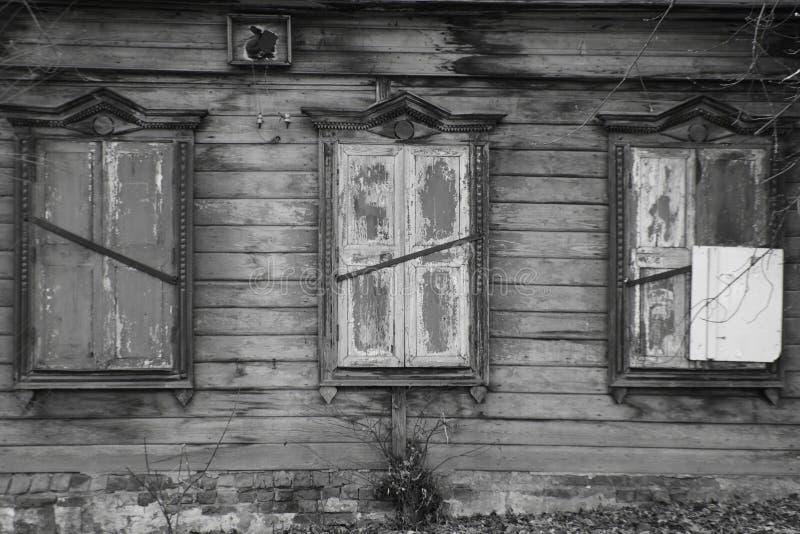 Oud verlaten blokhuis in zwart-wit De vensters van het huis zijn shuttered stock fotografie