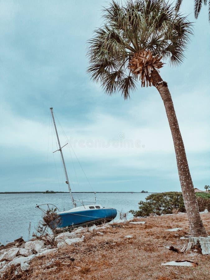 Oud verlaten bootjacht op overzeese oceaankust royalty-vrije stock afbeelding