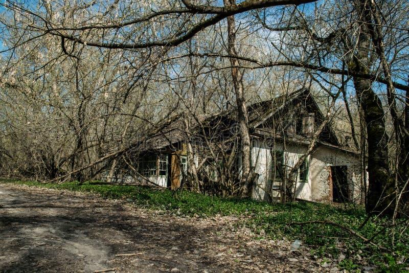 Oud verlaten buitenhuis in de uitsluitingsstreek Gevolgen van de kernramp van Tchernobyl royalty-vrije stock afbeeldingen