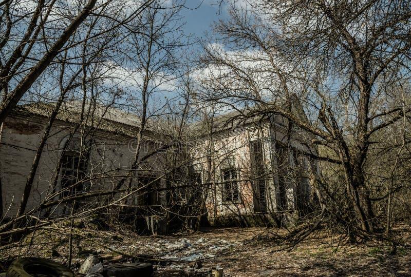 Oud verlaten buitenhuis in de uitsluitingsstreek Gevolgen van de kernramp van Tchernobyl stock foto