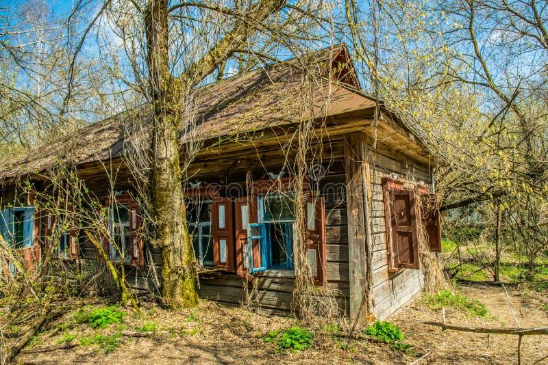 Oud verlaten buitenhuis in de uitsluitingsstreek Gevolgen van de kernramp van Tchernobyl stock foto's