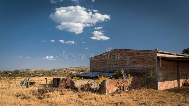 Oud verlaten die landbouwbedrijflandschap door blauwe hemel wordt gesteund royalty-vrije stock afbeeldingen