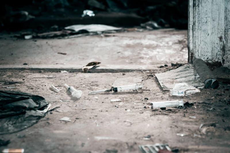 Oud verlaten huis en gebruikte plastic spuiten Het probleem van drugsverslaving in de maatschappij royalty-vrije stock foto