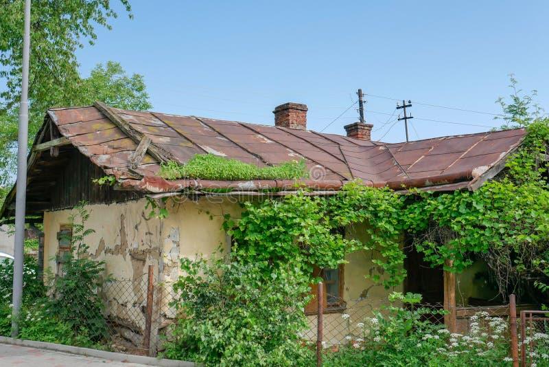 Oud verlaten huis met een roestig metaaldak stock foto's