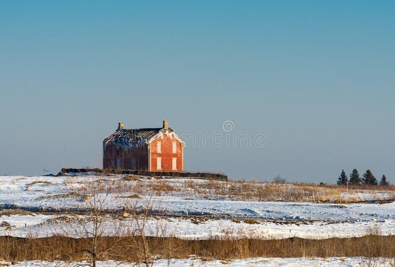Oud verlaten landbouwbedrijfhuis op een winters gebied stock fotografie