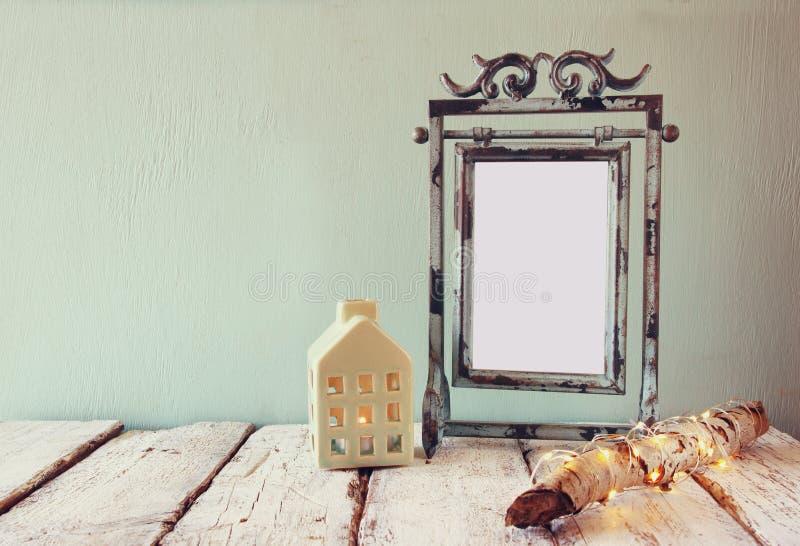 Oud victorian staal blauw leeg kader naast logboekboom met de lichten van feekerstmis en huislantaarn op houten lijst royalty-vrije stock afbeeldingen