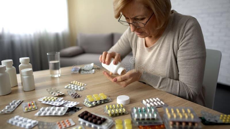 Oud wijfje die capsules van flessenself-medication de obsessie van de pillenverslaving nemen stock foto's