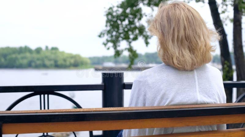 Oud wijfje die rivier, het denken bekijken aan het leven, plattelandskalmte, rust royalty-vrije stock fotografie