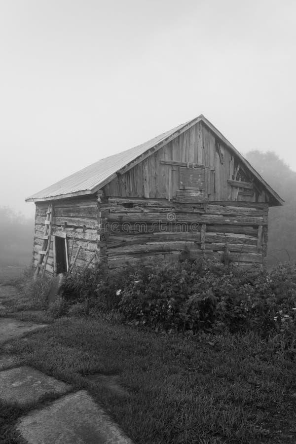Oud wijnoogst gezaagd blokhuis in mistbw stock fotografie