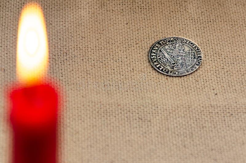 Oud zilveren muntstuk en brandende kaars stock fotografie