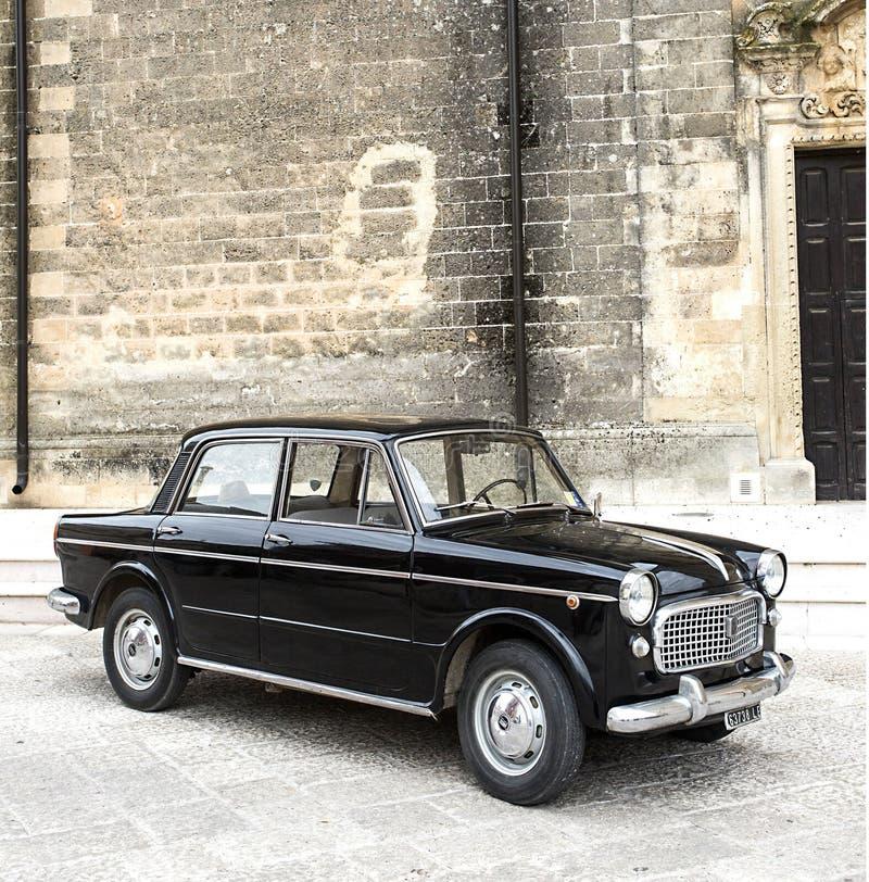 Oud zwart Fiat op een stadsstraat stock foto's