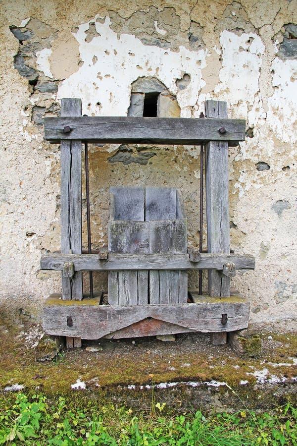 Oude Antieke houten wijnpers voor de oude muur stock foto
