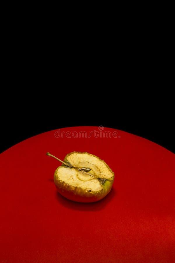 Oude appel in een besnoeiing op een rood-zwarte achtergrond royalty-vrije stock afbeeldingen