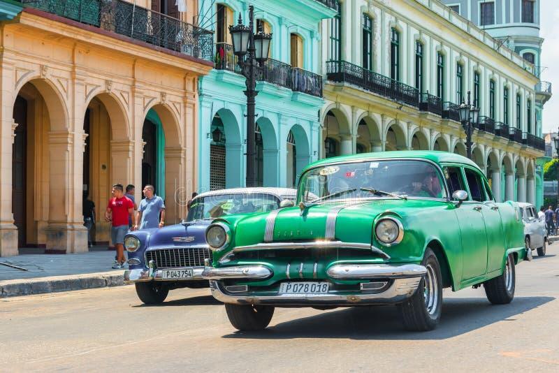 Oude auto's naast traditionele gebouwen in Oude Havan stock foto