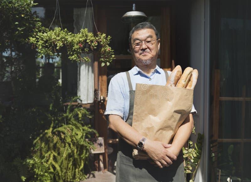 Oude Aziatische kerel met gebakken goederendocument zak stock foto's