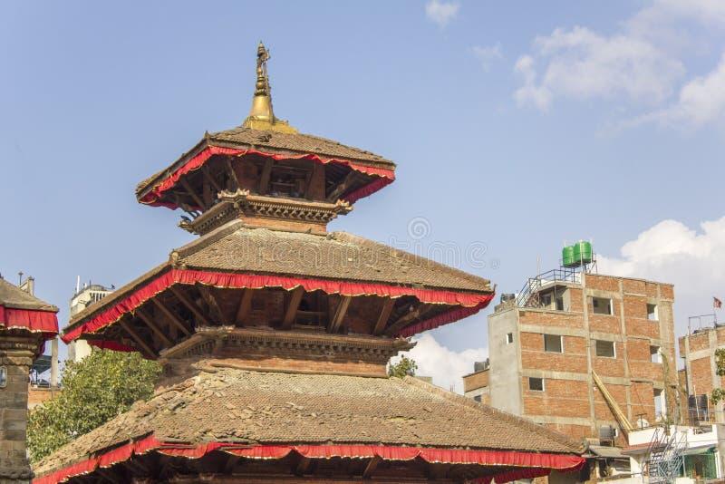 Oude Aziatische tempelpagode tegen stedelijke huizen en blauwe hemel stock afbeeldingen