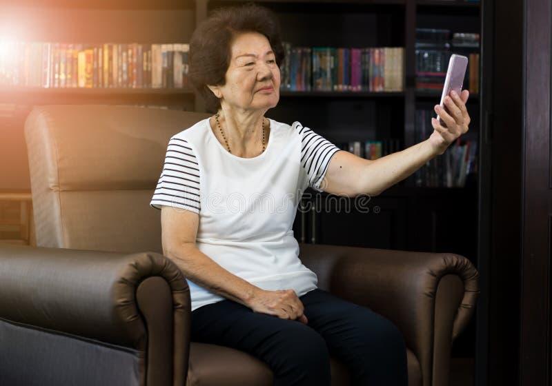 Oude Aziatische vrouw die smartphone gebruiken om te nemen selfie stock fotografie