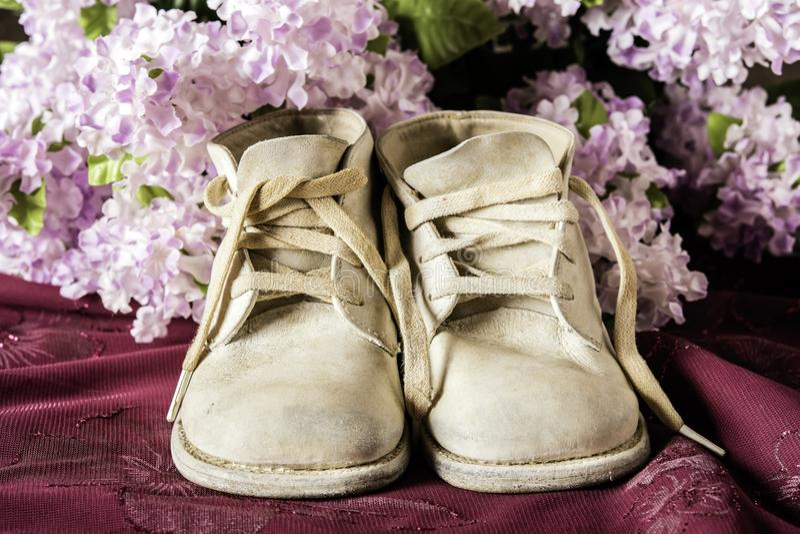 Oude Babyschoenen op Purpere Kleding royalty-vrije stock afbeeldingen