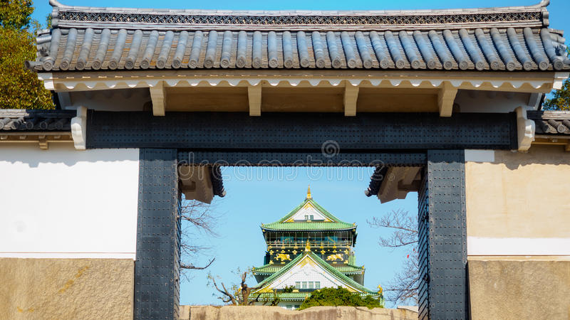 Oude bakstenen muur en ceramisch dak van het kasteel van Osaka met blauwe hemel stock foto