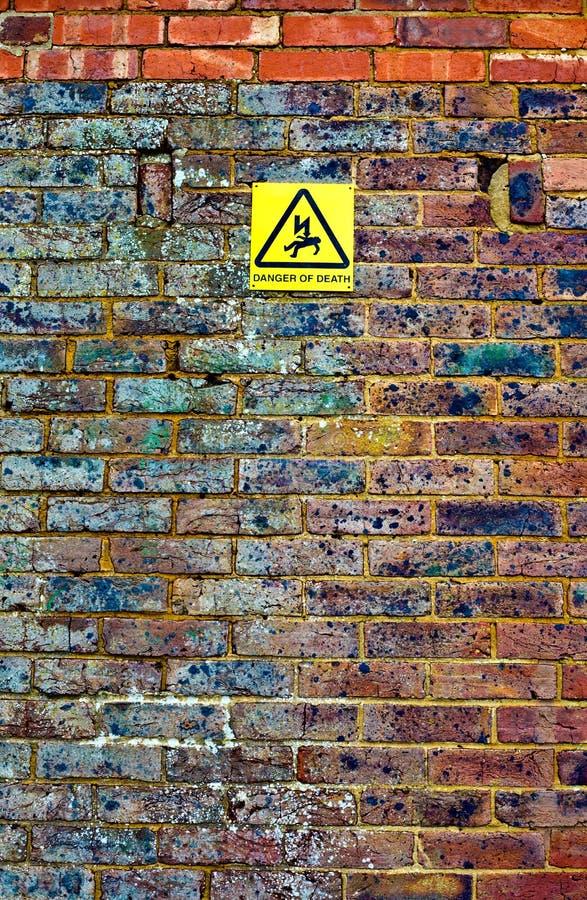 Oude bakstenen muur met waarschuwingssein royalty-vrije stock afbeelding