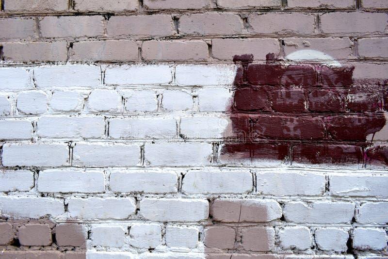 Oude bakstenen muur met witte en rode verfvlekken royalty-vrije stock afbeeldingen