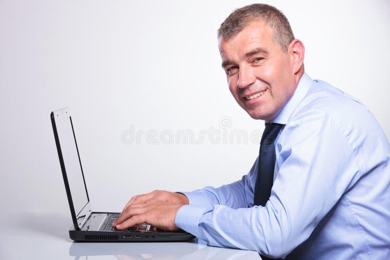 Oude bedrijfsmens die aan zijn laptop werken royalty-vrije stock foto