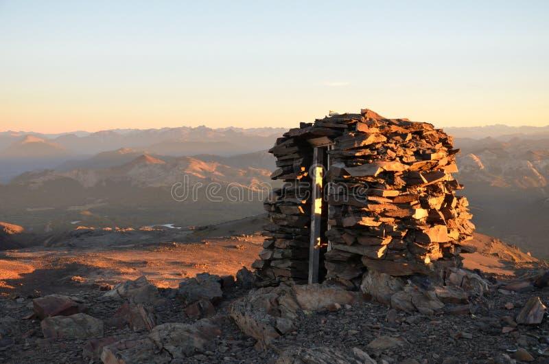 Oude bergschuilplaats in de zonsondergang bergen op de rug stock foto