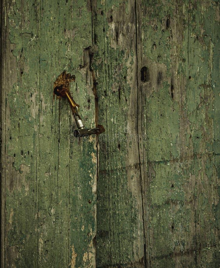 Oude beschadigde langzaam verdwenen groene houten deur met een klink van Sicilië stock afbeelding