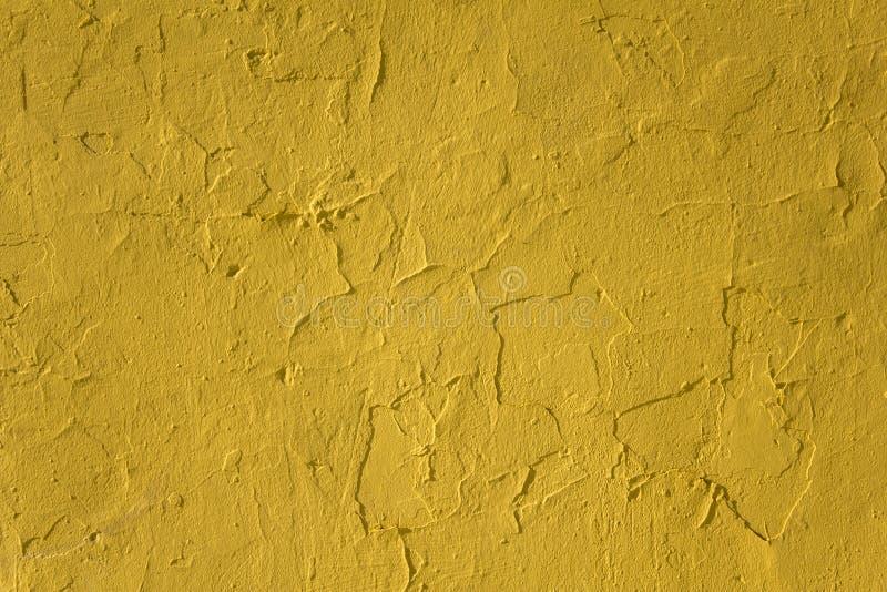 Oude beschadigde pellende gele concrete muur met barsten en schaduwen Ruwe Oppervlaktetextuur royalty-vrije stock foto's