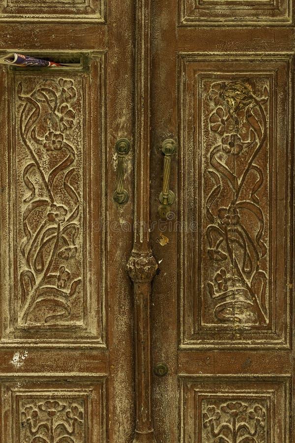 Oude beschadigde verfraaide langzaam verdwenen bruine historische houten deur met handvatten en krantengroef van Sicilië stock afbeelding