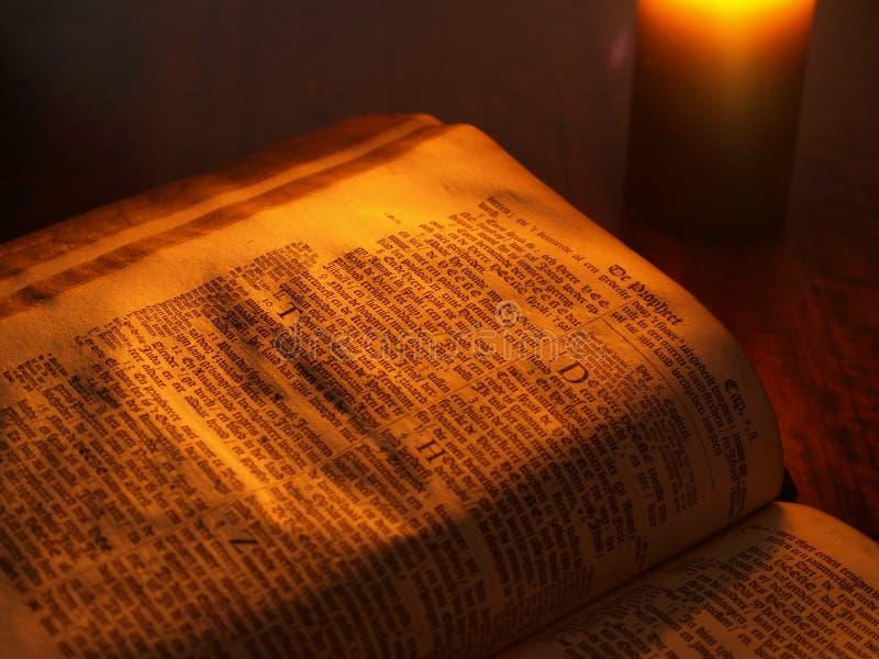 Oude bijbel door kaarslicht royalty-vrije stock afbeeldingen