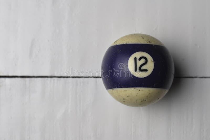 Oude biljartbal nummer 12 gestreepte wit en purper op witte houten lijstachtergrond, exemplaarruimte stock afbeelding