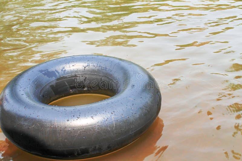 Oude binnenbanden met waterdalingen en bezinning van de zon die op een rivier drijven royalty-vrije stock fotografie