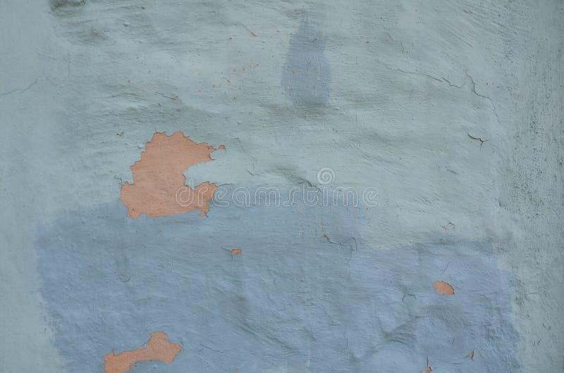 Oude blauwe afschilferende verf op muur met sinaasappel onderaan royalty-vrije stock foto