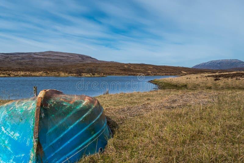 Oude blauwe boot dichtbij een meer stock foto