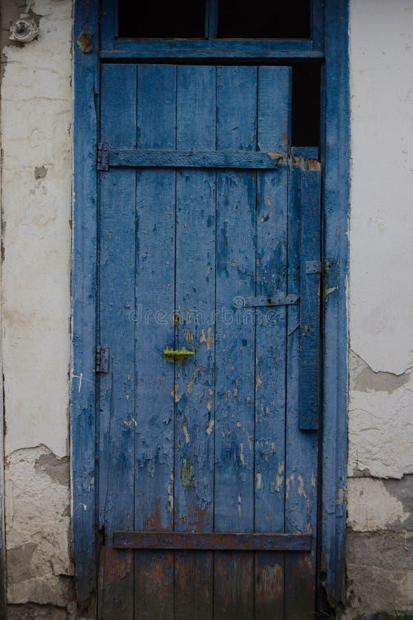 Oude blauwe deur Gebarsten verf Oude witte muur royalty-vrije stock afbeelding
