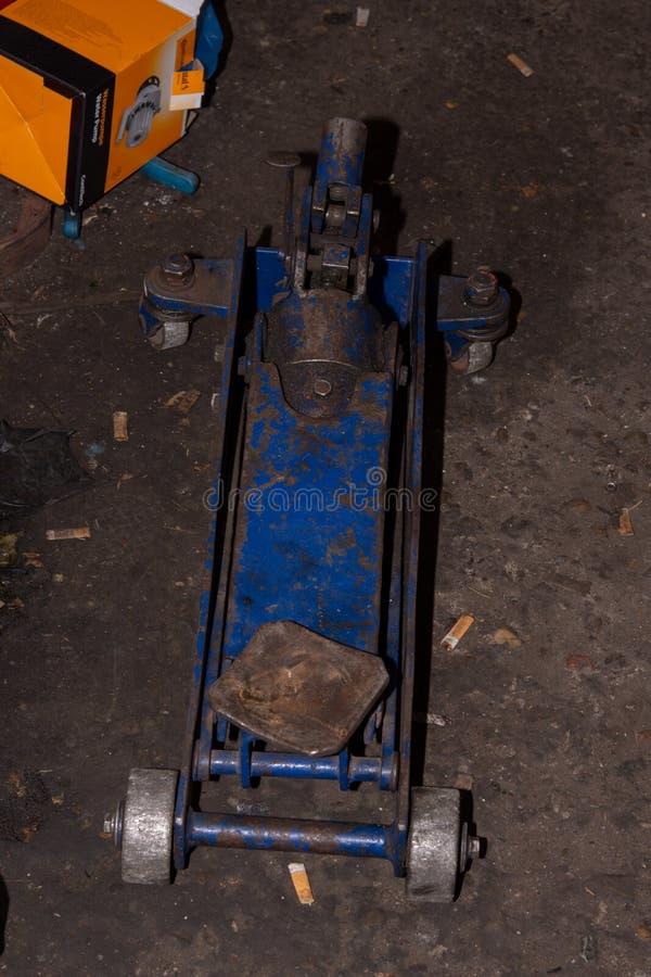 Oude blauwe hydraulische vloerhefboom of autohefboom op de vloer royalty-vrije stock afbeelding