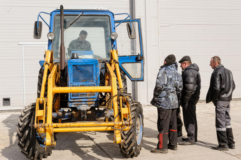 Oude blauwe Witrussische tractor met bestuurder en arbeiders royalty-vrije stock foto's