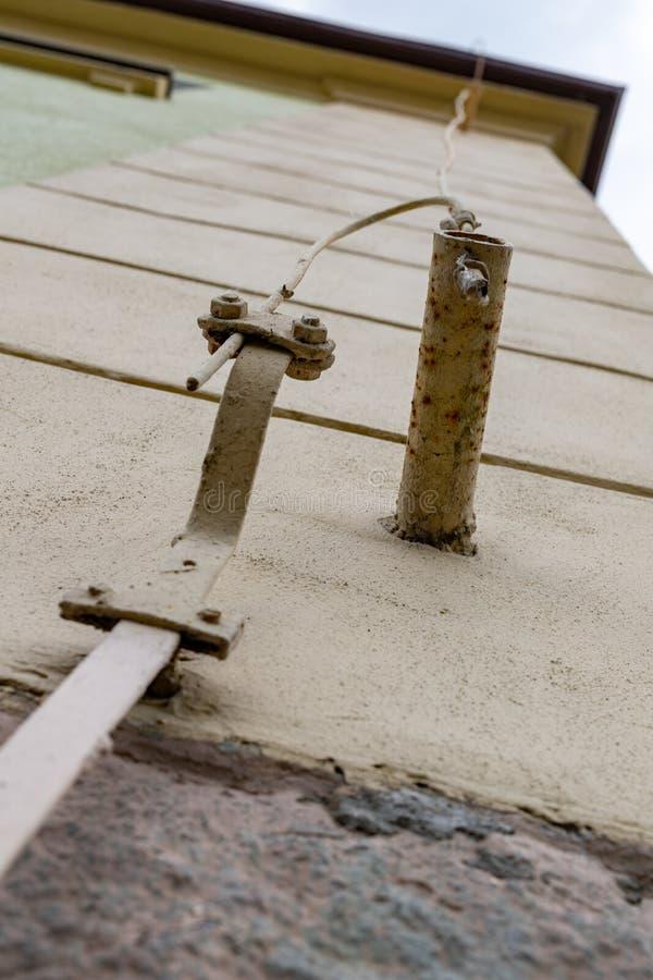 Oude bliksembescherming in een losgemaakt huis De kabels van de bliksembescherming stock foto